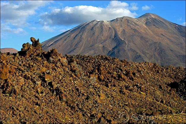 "Tromen. Lavas have a patina of iron oxides that lets them appear dark red or rust brown. (© <a href=""http://www.georouteandine.fr/English/expedition/geological_localities.php?date=tromen"" target=""_blank"">The Andean Geotrail - project</a>)"