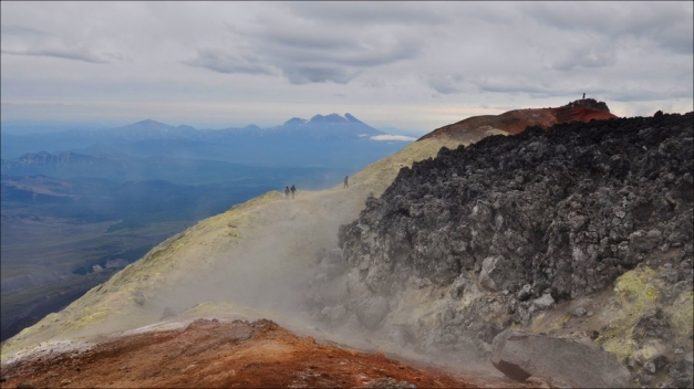 """Hikers leisurely perambulating along Avachinsky's crater rim in this otherworldly (or rather hellish) ambience... probably warm and cosy too ;) . (© Travel Company <a href=""""http://www.volcanoesland.com/attractions/avachinsky/"""" target=""""_blank"""">Volcanoes Land</a>)"""